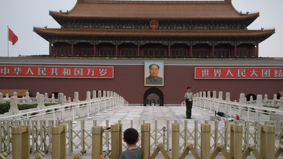 A boy views a portrait of former Chinese communist leader Mao Zedong before the lowering of the flag ceremony in Tiananmen Square