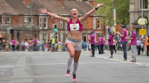 A competitor celebrates crossing the line in the Flora Women's Mini Marathon on Monday