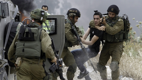 Israeli soldiers detain a Palestinian protester following a demonstration against the expropriation of Palestinian land by Israel
