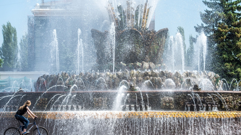 A woman rides her bike near the famous 'Druzhba narodov' ('Friendship of nations') fountain in Moscow, Russia