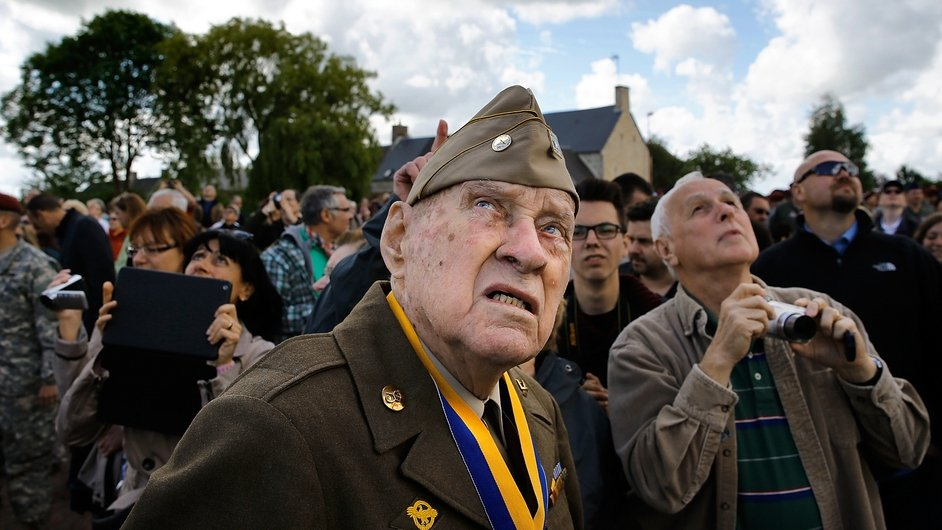A Normandy veteran looks on as paratroop veterans drop into a ceremony ahead of the 70th anniversary of the D-Day landings