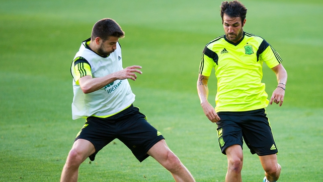 Gerard Pique (L) duels for the ball with Cesc Fabregas of Spain during a training session last week