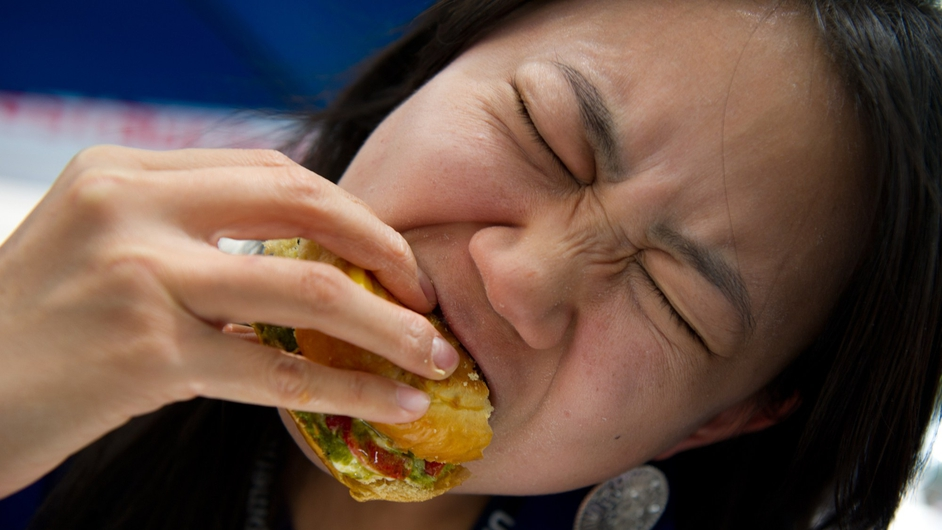 A patron takes a bite of a grasshopper burger during a global Pestaurant event held in Washington DC