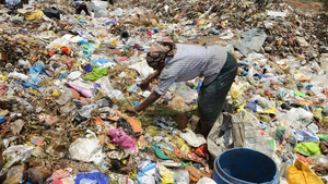 An Indian woman collects recyclable items at a garbage dump yard in Hyderabad, India, on World Environment Day