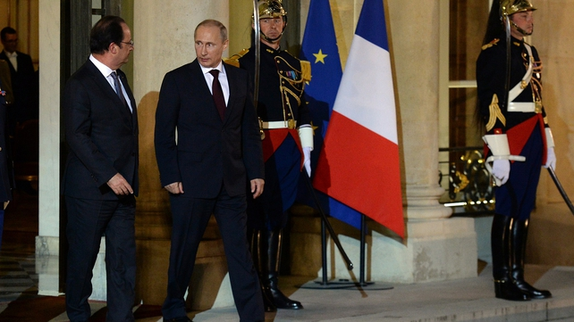French President Francois Hollande (L) escorts Russian President Vladimir Putin following their meeting and dinner at the Elysee Palace