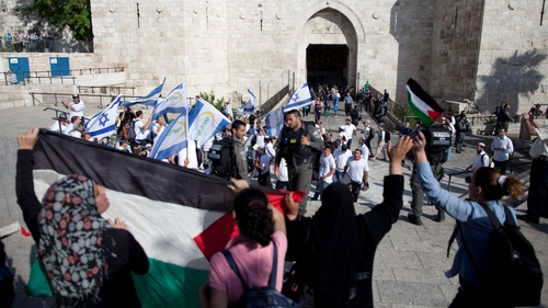 Palestinian protesters stand in front of Israelis with flags marking Jerusalem Day