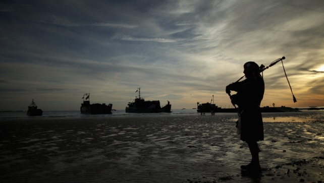 A piper plays a lament on Gold Beach as landing craft from the Royal Marines arrive at Arromanches, France