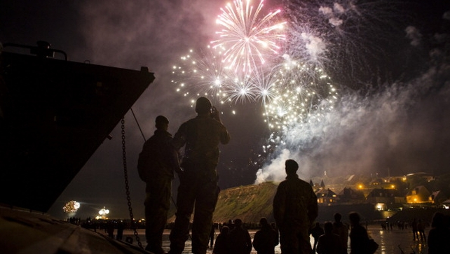 British soldiers stand on the debark ship as they watch fireworks in Arromanches, France