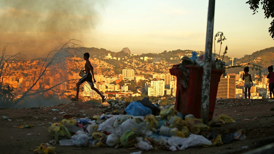 A fire burns due to the lack of government assistance of trash disposal in a community overlooking the Maracana World Cup stadium in Rio de Janeiro, Brazil