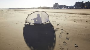 An early visitor sits with a sunscreen at the beach in Scheveningen, The Netherlands