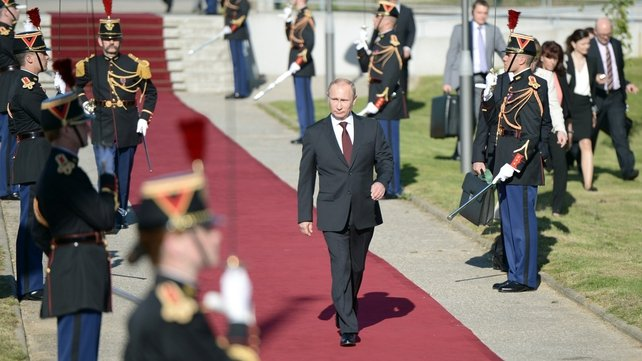 Russia's President Vladimir Putin walks past the French honour guard