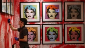 A Sotheby's employee hangs a print ahead of the first unauthorized retrospective of works by UK artist Banksy in London, England.