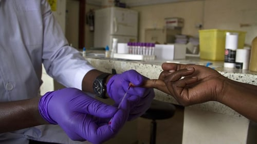 A lab technician draws blood from a patient for HIV testing at the Aids Information Centre in Kampala