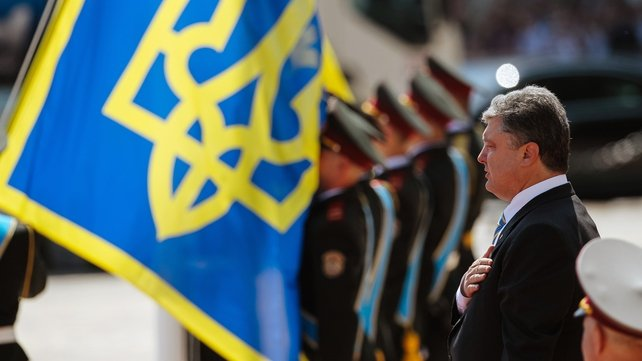 Petro Poroshenko sings the Ukrainian anthem during the flag raising ceremony after his inauguration