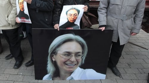 People hold photos as they attend a commemoration rally in honour Anna Politkovskaya in 2012