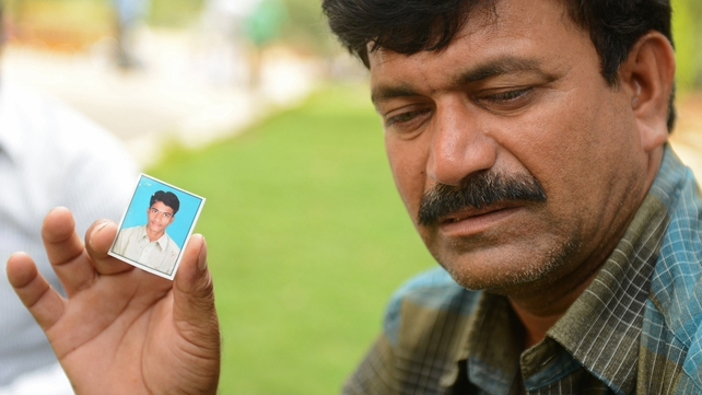 A father waits for news of his son who was among those washed away yesterday