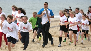 Olympic boxer Anthony Ogogo carries the Queen's Baton along the sea front in Suffolk, England