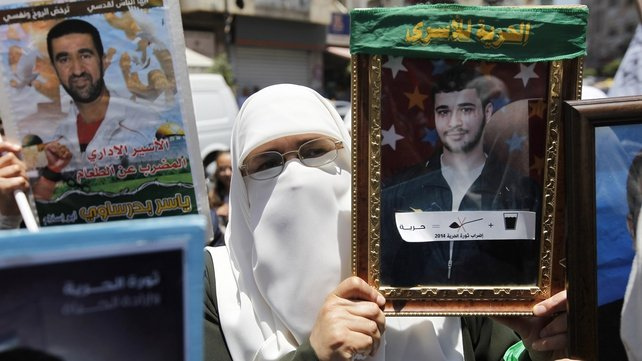 A Palestinian woman holds a portrait of a detainee in the West Bank city of Ramallah
