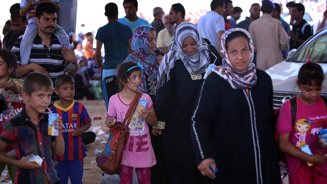 Iraqi families fleeing violence in the northern Nineveh province gather at a Kurdish checkpoint