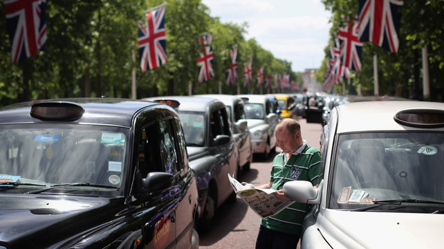 A London taxi driver looks at his phone on The Mall during the protest