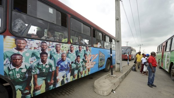 Commuters queue to board a bus in Lagos decorated with photographs showing 'Super Eagles' players