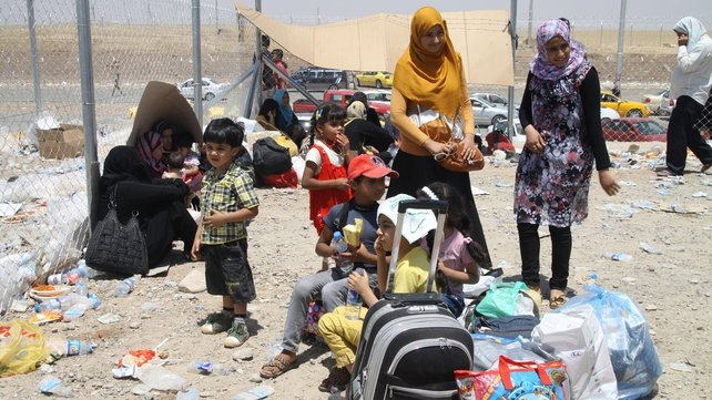 Iraqis who fled the violence in Mosul queue at a checkpoint in the Kurdistan region