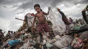 A young scavenger boy grabs plastic between tons of rubbish in the Anlong Pi in Siem Reap, Cambodia. Dozens of children scour the dump every day