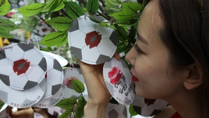 A South Korean woman kisses a paper football during an event to wish her country's team success in the World Cup