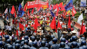 Filipino protesters are blocked by ant-riot police during a protest rally to mark the 116th year of Philippine Independence