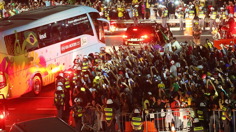 Fans cheer and take photos as the Brazilian team bus departs outside Itaquerao stadium