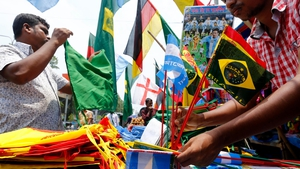 A street vendor displays small flags of Brazil and Argentina and other World Cup related products at a street market in Dhaka, Bangladesh