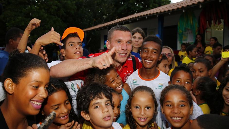 Germany's Lukas Podolski visits a school and kindergarten in Bahia, Brazil