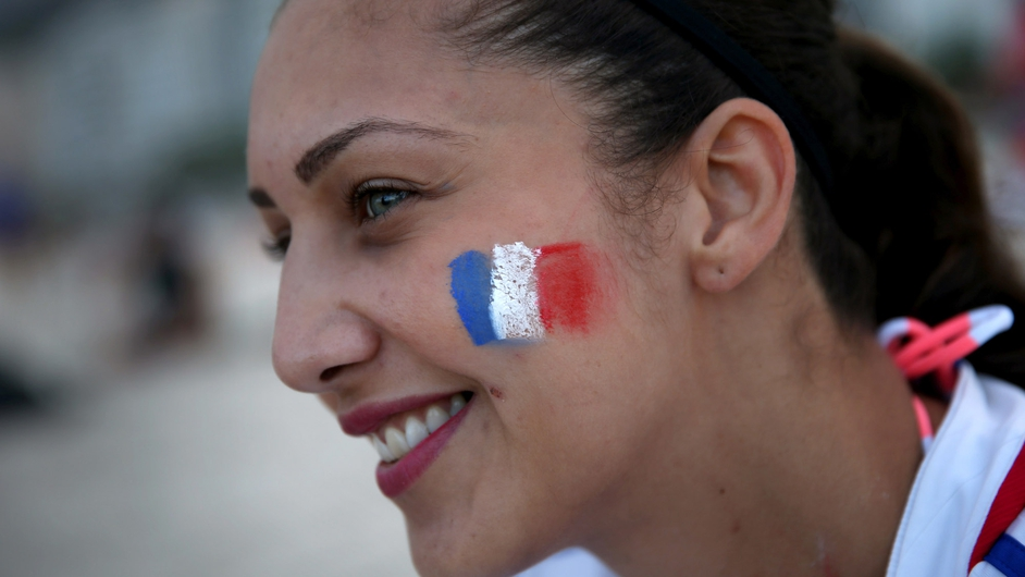 A French football fans sports her country's colours as she enjoys Copacabana beach before the start of the World Cup