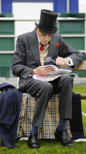 A racegoer checks the form with his magnifying glass at Epsom racecourse on Saturday