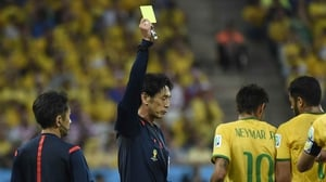Head match referee Yuichi Nishimura hands Neymar a yellow card in the first half