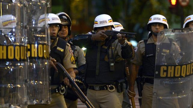 A police man aims his shotgun at demonstrators in Belo Horizonte