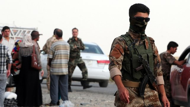 Armed men watch Iraqis who fled the violence in Mosul upon their arrival at a checkpoint in Erbil