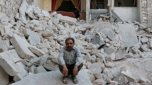A Syrian man sits on the rubble of a destroyed building following reported air strikes by government forces in the northern city of Aleppo