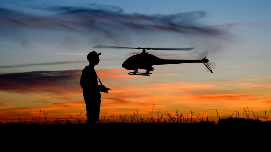 Yanik Wolter, 16-year old, controls a model helicopter during a sunset on a field in Gleidingen, Hannover, Germany
