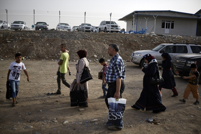 People fleeing violence cross a Kurdish checkpoint in Kalak after the city of Mosul was overrun by militants