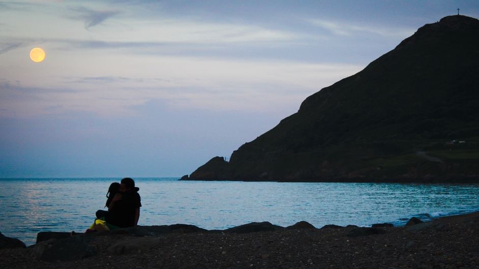 A young couple embrace under the full moon at Bray beach last night (Pic: Micheál Mac Suibhne)