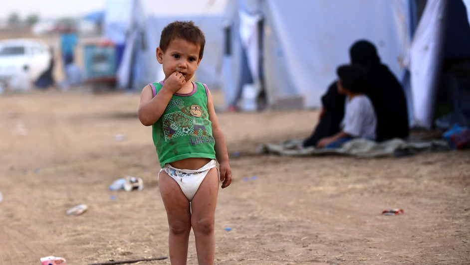 An Iraqi refugee child stands next to a tent at a refugee camp near the city of Erbil.