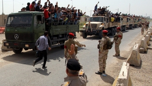 Iraqi men who volunteered to join the fight against a major offensive by jihadists in northern Iraq stand on army trucks.