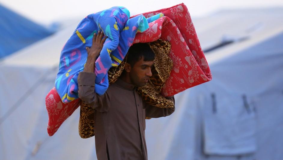 An Iraqi refugee man carries mattresses at a refugee camp near the city of Erbil.