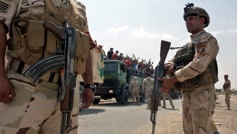 Iraqi military trucks transport Iraqi volunteers to Muthanna base in central Baghdad.