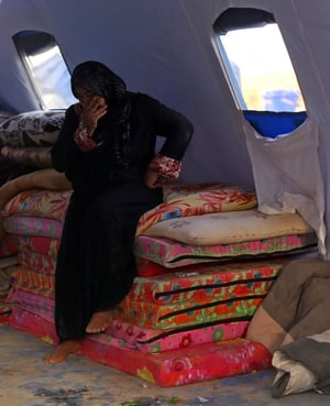 An Iraqi refugee woman sits inside a storage tent for mattresses at a refugee camp.