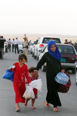 Iraqis who fled the violence in Mosul arrive at a checkpoint in Erbil.