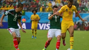 Mexico's Hector Herrera and Cameroon's Eric Maxim Choupo-Moting fight for the ball in rainy Natal
