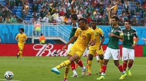 Choupo-Moting shoots on goal, while Mexican players pause play to call him offside (which the line-men did as well)