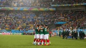 As time expires, the Mexican team celebrates their country's first World Cup win over an African side, with the final score standing at 1-0